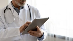 Old male doctor holding modern digital tablet computer standing in hospital, close up view. Senior middle aged professional medic wears white coat and stethoscope using healthcare ehealth application.