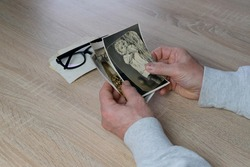 old male hands hold retro family photos over an album with vintage monochrome photographs in sepia color, genealogy concept, ancestral memory, family tree, childhood memories