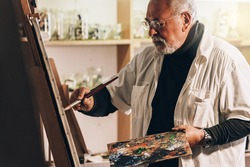 Old man artist painting oils in his studio. Artist Concept.