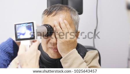 Old man checking on eye