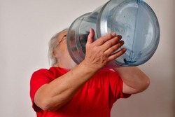 Old man drinking from a 5 gallon water bottle. Thirsty man drinks from a 5 gallon water bottle. Thirsty old man drinking from a large bottle.