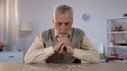 Old man exercises with puzzle, suffers cognitive impairment, Alzheimer symptom