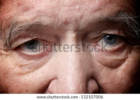 old man face part closeup eyes looks at camera