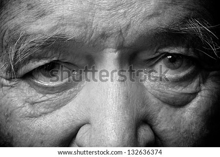old man face part closeup eyes looks at camera monochrome image