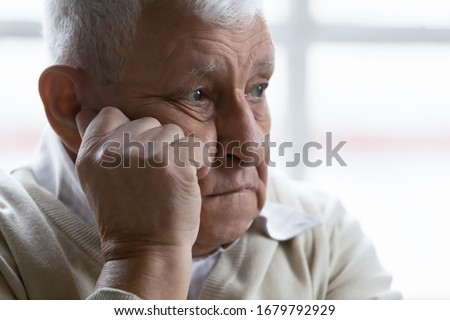 Old man feeling disappointed, lost in sad thoughts close up portrait. Baby boomer generation 80s grandfather suffers from loneliness, chronic or dementia senile diseases, life troubles regrets concept