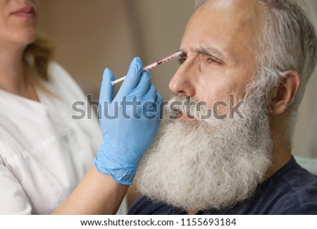 Old man getting wrinkle treatment with hyaluronic acid in beauty parlor #1155693184