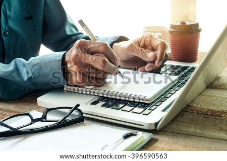 old man hand writing with a pen in a notebook,Handwriting  on office wood table with laptop computer