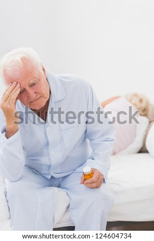 Old man having a headache while woman sleeping on the bed