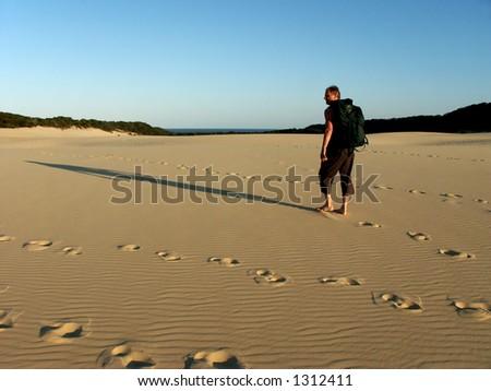 old man hiking in sand dunes on fraser island australia