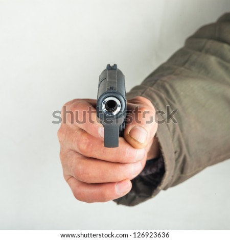 old man hold pistol pointing to the camera