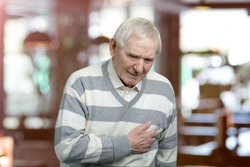 Old man holding breast because of heart infarction. Painful senior man with pain on heart, heart attack. Abstract blurred background.