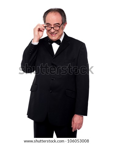 Old man holding his eyeglasses and smiling at camera. Fashion portrait