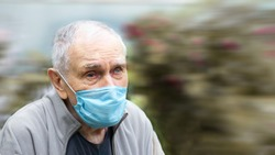 old man in a medical mask. old man wears a mask outdoors to avoid getting infected with the Corvette-19 virus. Prevention of viral diseases in the context of a pandemic. Copy space
