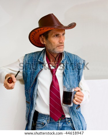 Old Man in cowboy hat with mug and pipe