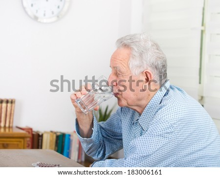 Old man in pajamas drinking glass of water and have pills blister on table