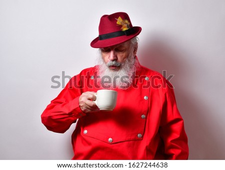 Old man in red western bib shirt blowing into his coffee cupMature gentleman enjoying a cup of coffee and blowing into his cup Stok fotoğraf ©