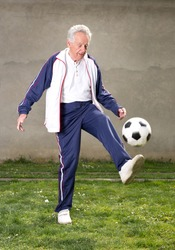 Old man in seventies kicking a soccer ball in courtyard