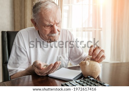 old man in the pandemic counts pennies from the pension fund. Concerned about lockdown, an elderly man puts money in a piggy bank. pensioner calculates the budget of his pension.