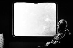 Old man in train. Black and white photo. Lonely passenger looks out window. Sad mood, nostalgia