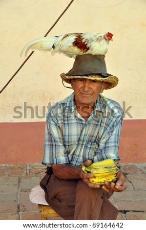 old man in trinidad, cuba, with chicken on head