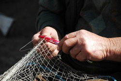 old man is repairing fishing net with hands.