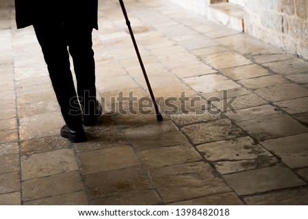 Old man legs walking with walking stick on stone tiles