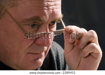 old man looking from under the glasses