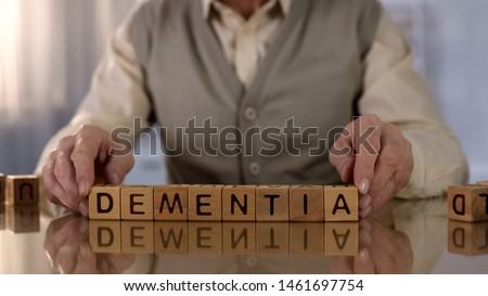 Old man making word dementia of wooden cubes on table, brain disease, health Сток-фото ©