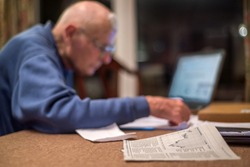 Old man of 93 using his laptop to check his finances online,very challenging for old people.
