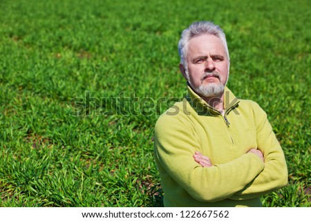 Old man on a green field with hands crossed