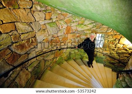 Old man on the stairs of tower