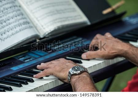 Old man playing a piano keyboard