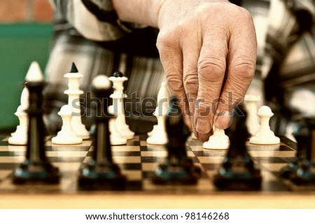 old man playing chess and make the first move