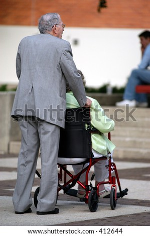 Old man pushes his wife in a wheel chair