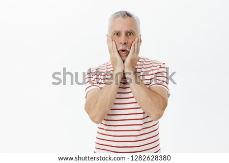 Old man reacting on shicking scene touching cheeks from amazement and folding lips listening amazing, unbelievable stories standing in trendy striped t-shirt over gray background