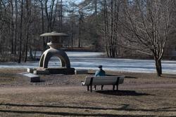 Old man resting in the spring park near strange sculpture