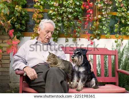 Old man resting on bench and cuddling dog and cat