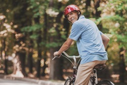 Old Man Riding on Bicycle in Park in Summer. Healthcare Concept. Relaxing in Park. Active Rest Concept. Riding on Bicycle. Smiling Grandfather. Man with Gray Hair. Healthy Lyfestyle in Summer.