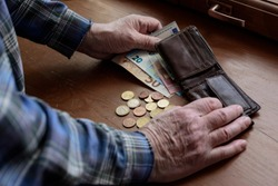 Old man's hands, count money, Euros. The concept of poverty, low income, austerity in old age.