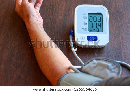 Old Man's health check blood pressure and heart rate at home with digital pressure very high blood pressure test results.Risk for cardiology.Need some medicine.Health and Medical concept.
