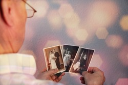 old man's male hands hold old retro family photos in sepia color and looks at photographs of his and his sisters, made in 1963 - 1964, genealogy concept, ancestral memory, family