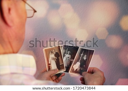 old man's male hands hold old retro family photos in sepia color and looks at photographs of his and his sisters, made in 1963 - 1964, genealogy concept, ancestral memory, family  ストックフォト ©