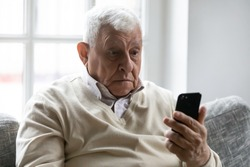 Old man sit on sofa hold smartphone look at device screen feels confused shocked by received sms message. Older generation and modern gadgets apps usage difficulties, broken cell, need repair concept