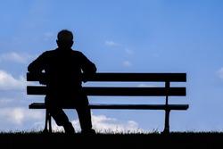 old man sitting alone on park bench under tree