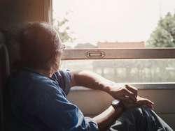 Old man sitting beside the window and looking out the train window