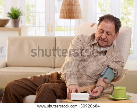 Old man sitting in armchair at home, measuring his blood pressure, smiling.