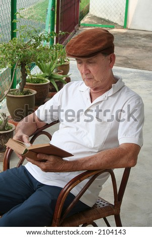 Old man sitting on the chair reading a book
