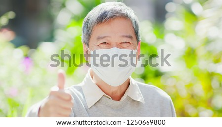 old man smile show thumb up and wear mask with nature green background #1250669800