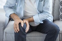 Old man suffering from knee pain sitting sofa