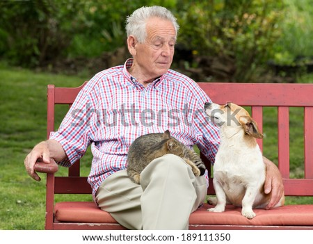 Old man talking to his dog while cat resting in his lap